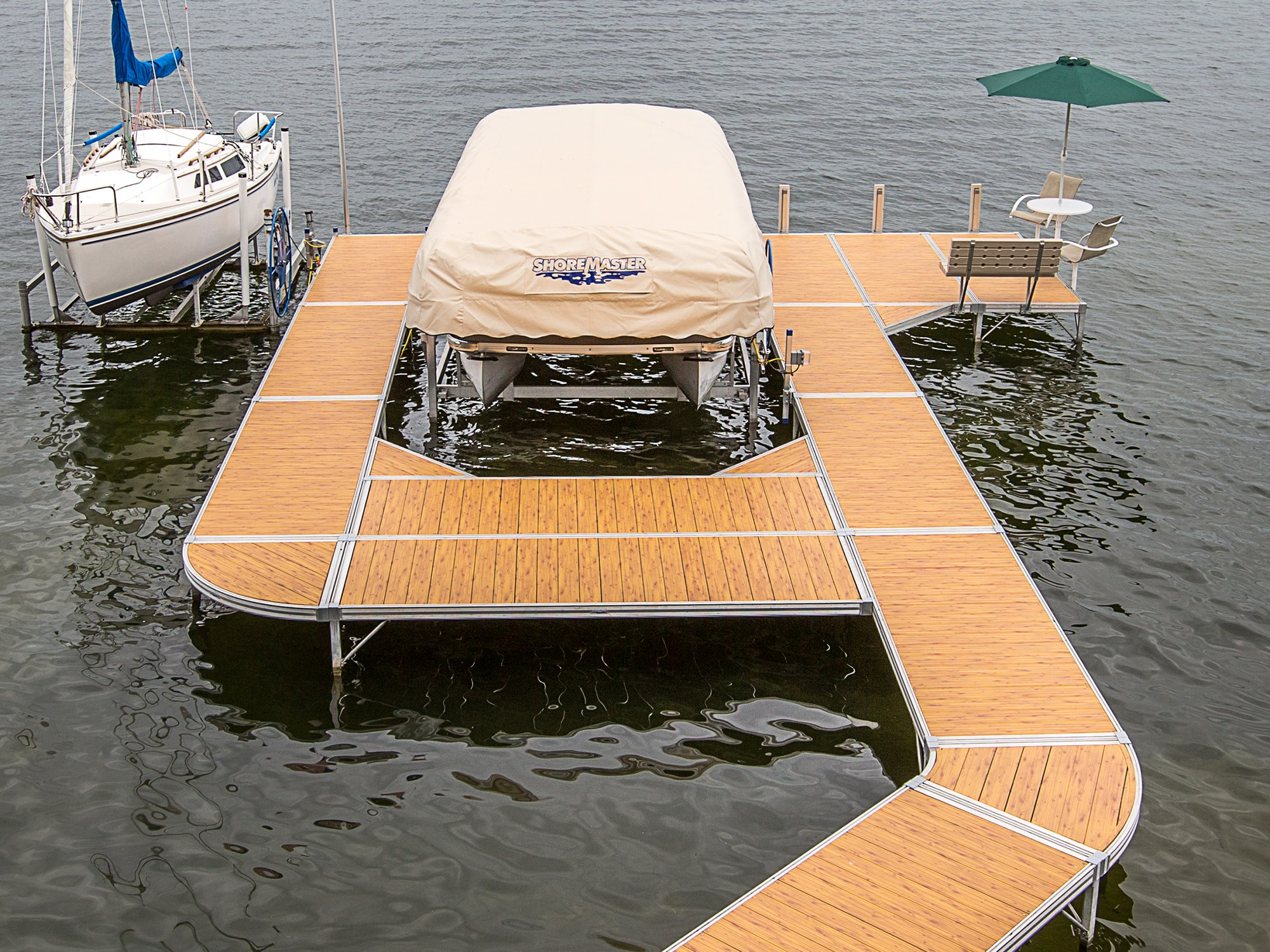 ShoreMaster Infinity RS4 Dock with Traditional Woodgrain Decking, Pontoon Lift, Dock Bench, Dock Furniture and Sailboat.